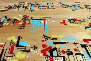 Calligraphie expérimentale sur les étagères d'une bibliothèque, en collaboration avec les Ateliers Walser